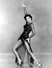 1953: Full-length image of American actor and dancer Cyd Charisse dancing with one hand held above her head in a scene from director Vincente Minnelli's film 'The Band Wagon'. She is wearing a sequined gown with an open front slit.